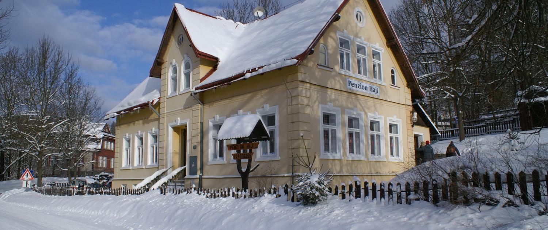 Příjezdová cesta s penzionem Hají v zimě